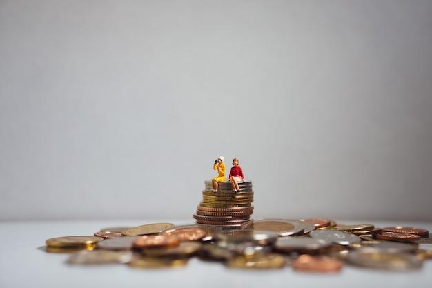 Miniaturowi ludzie, pary kobiety obsiadanie na stert monetach