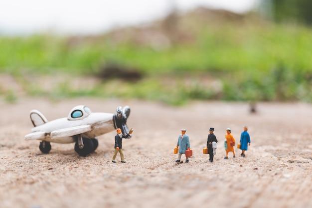 Miniaturowi ludzie: podróżni trzymający bagaż podręczny wsiadają do samolotu