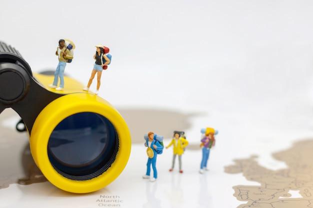 Miniaturowi ludzie: podróżnik z plecakiem idący ścieżką turystyki. koncepcja podróży i lata