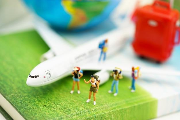 Miniaturowi ludzie, podróżnik z plecakiem na szlaku turystyki samolotem.