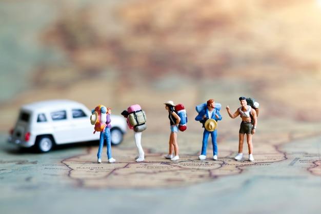 Miniaturowi ludzie: podróżnik z plecakiem stojącym na mapie vintage.