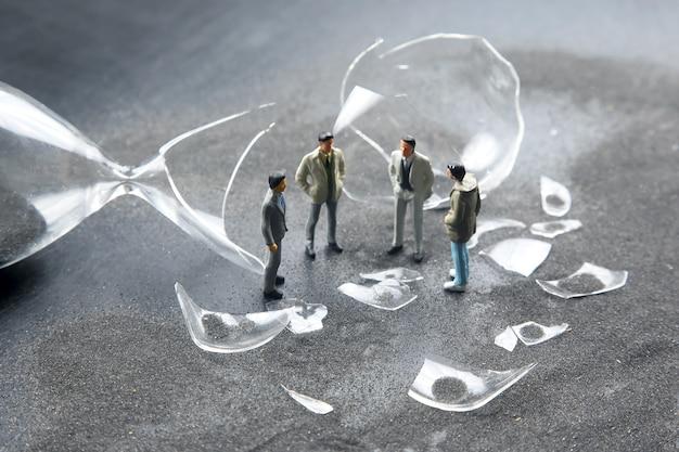 Miniaturowi ludzie. postacie ludzie stoją w pobliżu zepsutej klepsydry. kryzys biznesowy. zatrzymać proces czasu