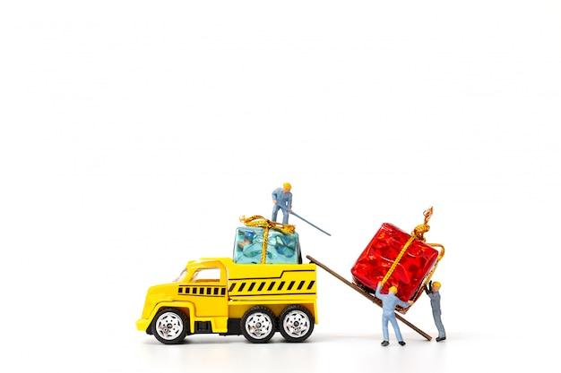 Miniaturowi ludzie pracujący na pudełku