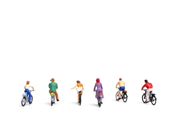 Miniaturowi ludzie: przyjaciel grupy przejażdżki bicykl odizolowywa na białym tle
