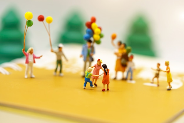 Miniaturowi ludzie, rodzina i dzieci, bawią się kolorowymi balonami.