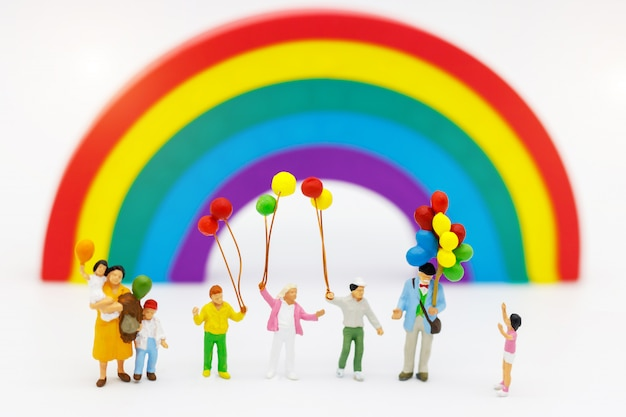 Miniaturowi ludzie: rodzina i dzieci cieszą się kolorowym balonem.