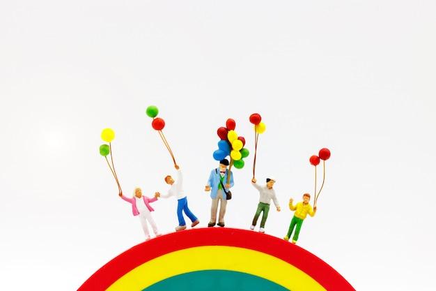 Miniaturowi ludzie: rodzina i dzieci cieszą się kolorowymi balonami na tęczy.
