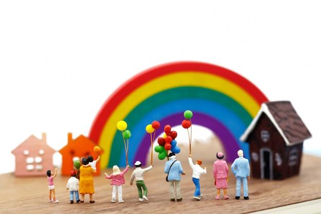 Miniaturowi ludzie, rodzina i dzieci cieszą się kolorowymi balonami.