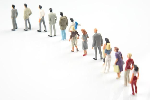 Miniaturowi ludzie. różni ludzie stoją w kolejce jeden po drugim na białym tle. komunikacja społeczeństwa różnych pokoleń