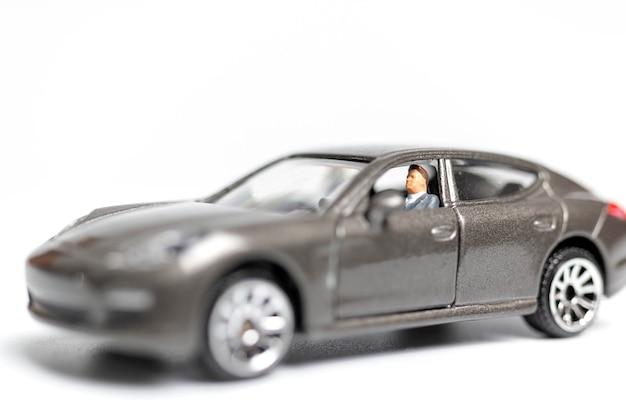 Miniaturowi ludzie siedzi na samochodzie z kopii przestrzenią
