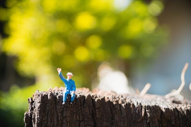 Miniaturowi ludzie, starego człowieka obsiadanie na zielonym natury tle używać dla wakacyjnego pojęcia