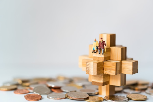 Miniaturowi ludzie, starsi ludzie siedzący na drewnianym