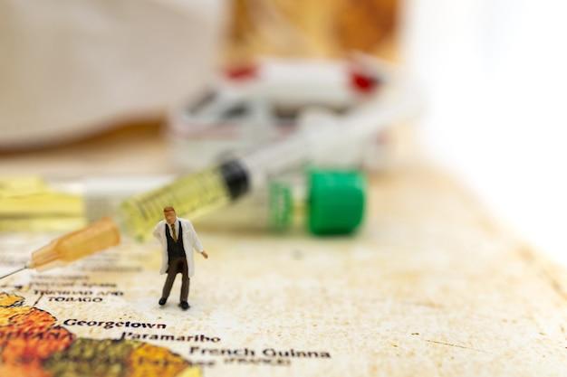 Miniaturowi ludzie stoją na mapie świata z karetką, maską medyczną i strzykawką szczepionki covid-19. pojęcie medyczne szczepionki i opieki zdrowotnej.