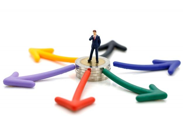 Miniaturowi ludzie stojący na monetach z wyborem ścieżki strzałek.
