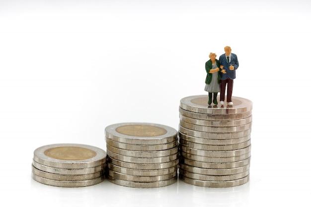 Miniaturowi ludzie: szczęśliwa starsza para stoi na stosie monet. pojęcie emerytury.