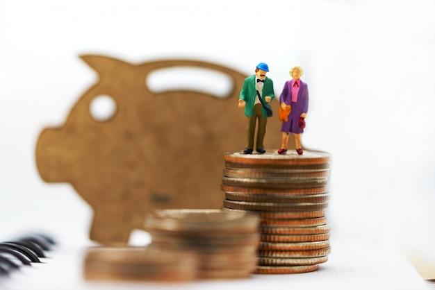 Miniaturowi ludzie, szczęśliwa starsza para stoi na stosie monet z drewnianą świnią