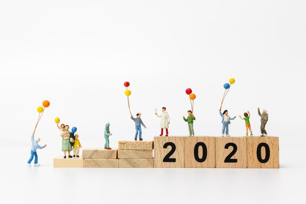 Miniaturowi ludzie: szczęśliwy rodzinny balon na drewnianym bloku numer 2020