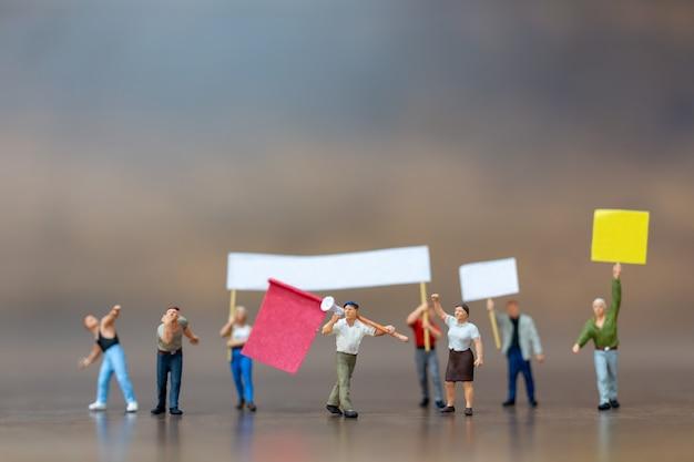 Miniaturowi ludzie, tłum demonstrantów podnosił ręce i krzyczał