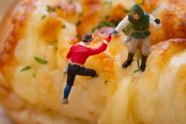 Miniaturowi ludzie: wspinacz wspina się na deser.