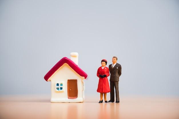 Miniaturowi ludzie, zbliżenie mężczyzna i kobieta stoi z mini domem używać jako związek i rodzinny co