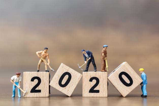 Miniaturowi ludzie: zespół pracowników tworzy drewniany blok o numerze 2020