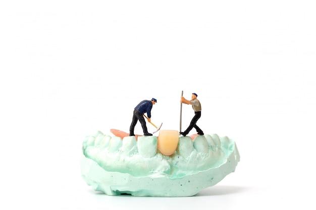 Miniaturowi ludzie, zespół robotników naprawiający ząb