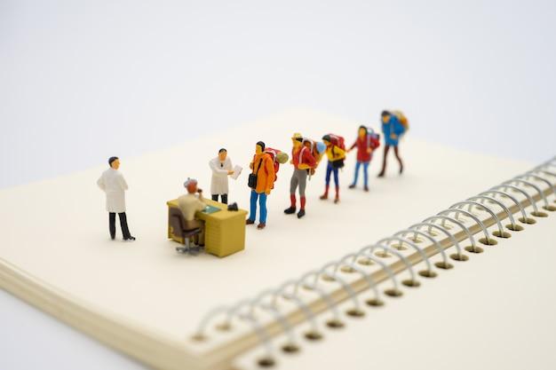 Miniaturowi podróżnicy i lekarz sprawdzają ciała turystów przed wejściem