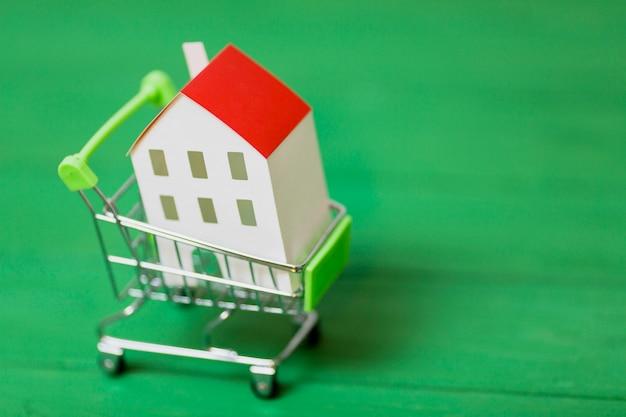 Miniaturowy biały dom wśrodku wózek na zakupy na zielonym tle