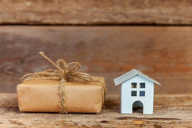 Miniaturowy biały domek z zabawkami i pudełko owinięte papierem rzemieślniczym na starym drewnianym tle