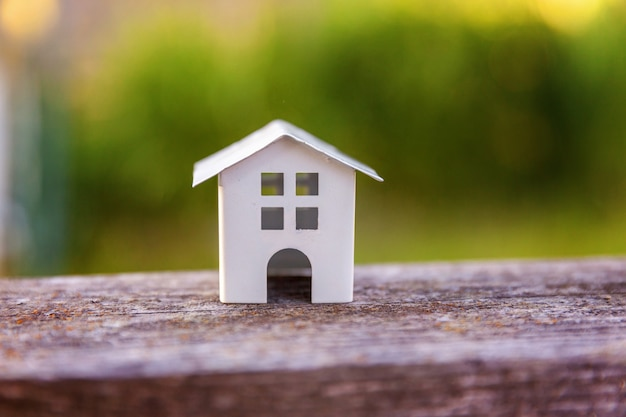 Miniaturowy biały domek z zabawkami na drewnianym tle w pobliżu zielonego tła ekologicznego