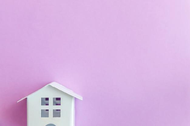 Miniaturowy biały zabawka dom na fioletowym fioletowym tle pastel