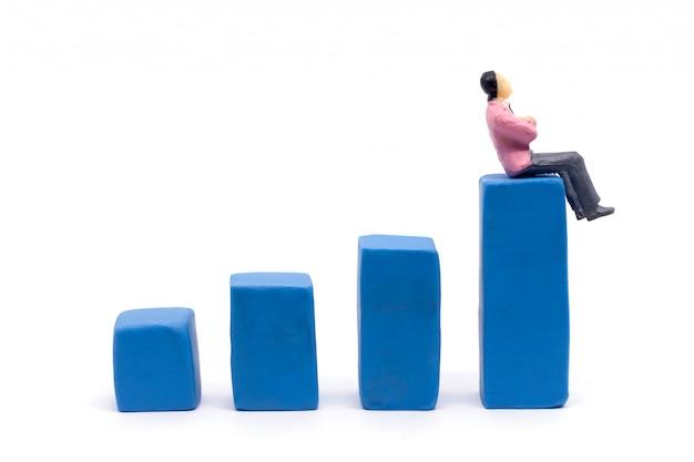 Miniaturowy biznesmen i wykres na białym tle, biznesowy wzrostowy pojęcie