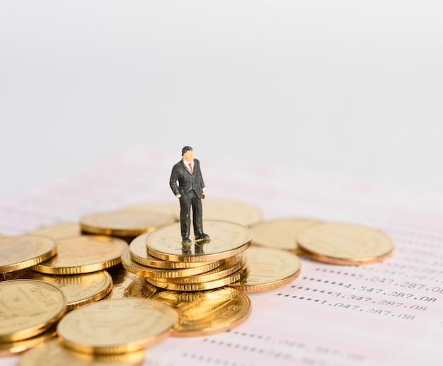 Miniaturowy biznesmen, odnoszący sukcesy, stoi na złotych monetach na tle banku książki