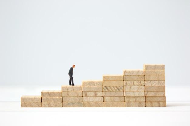 Miniaturowy biznesmen robi decyzi na drewnianym wykresie.
