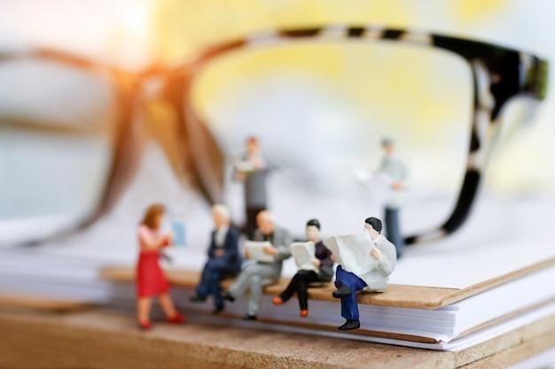Miniaturowy biznesmen siedzi na książkach.