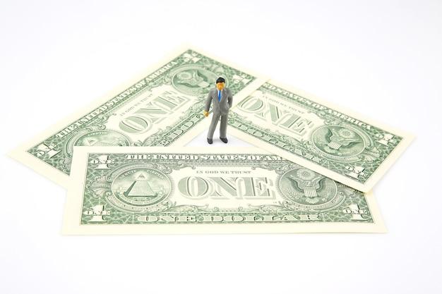 Miniaturowy biznesmen stojący na banknotach dolarowych na białym tle