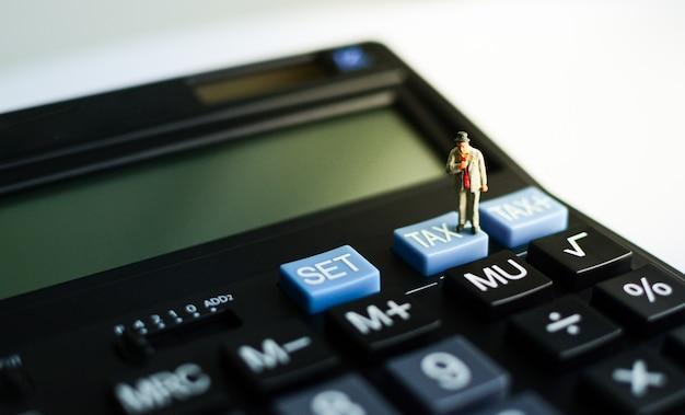 """Miniaturowy biznesmen stojący na niebieskim przycisku """"podatek"""" czarnego kalkulatora z efektem świetlnym po prawej stronie u góry, wykorzystujący jako zwrot podatku, pojęcie finansowe i biznesowe."""