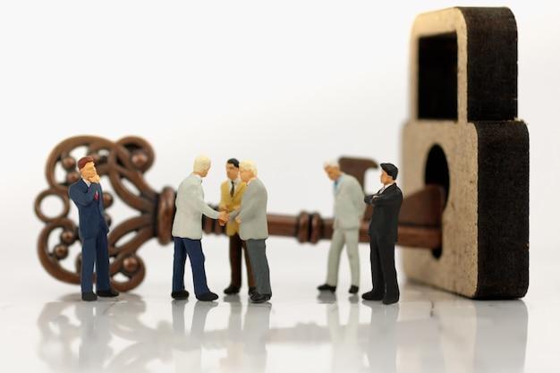 Miniaturowy biznesmen uścisk dłoni z odblokować klucze.