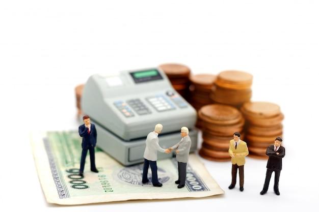 Miniaturowy biznesmen uścisk dłoni z stosem monet i bankomatem.