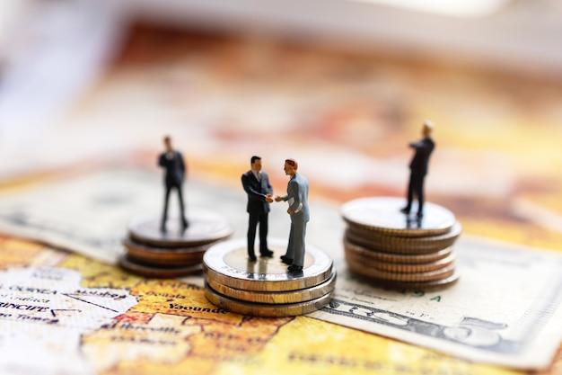 Miniaturowy biznesmen uścisk dłoni ze stosem monet na mapie świata, koncepcja inwestycji i biznesu
