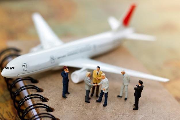 Miniaturowy biznesmena uścisk dłoni na książce z samolotem.