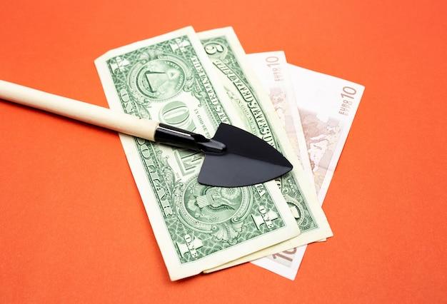 Miniaturowy czarny szpadel z drewnianą rączką z bliska na pomarańczowym tle z banknotami