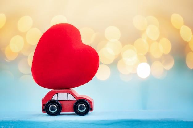Miniaturowy czerwony samochód niosący czerwone serce