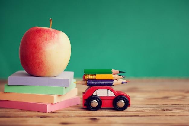 Miniaturowy czerwony samochód niosący kolorowe kredki i czerwone jabłko i stos papierów na drewnianym stole. powrót do koncepcji szkoły