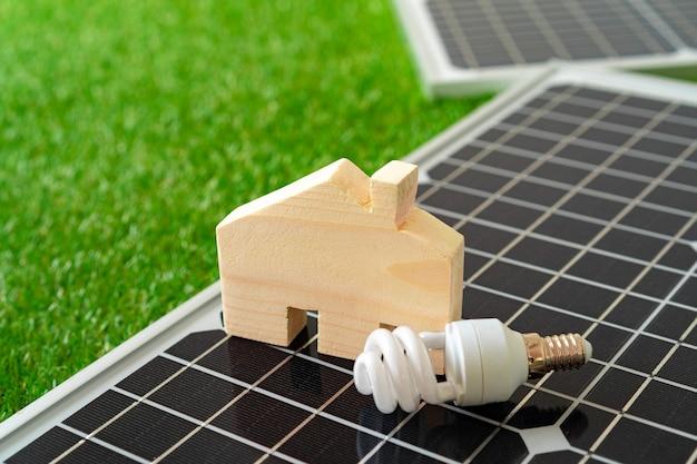 Miniaturowy dom drewniany i panel słoneczny z bliska