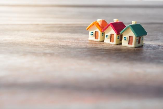 Miniaturowy dom na drewnianym tle. koncepcja inwestycji w nieruchomości.