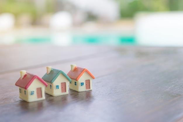 Miniaturowy dom na drewnianym tle. wizerunek dla majątkowej nieruchomości.