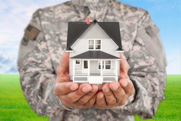 Miniaturowy dom w rękach żołnierza