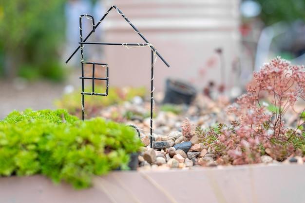 Miniaturowy domek stoi na kamykach wśród zieleni