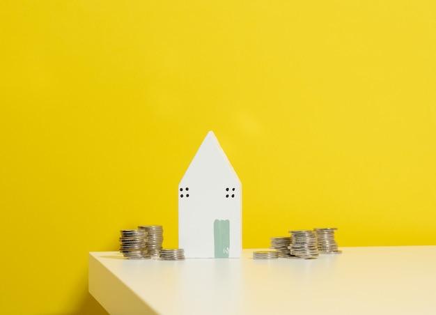 Miniaturowy drewniany dom i stos monet na białym stole. zakup nieruchomości, koncepcja hipoteki. wzrost cen nieruchomości, dotacje od państwa